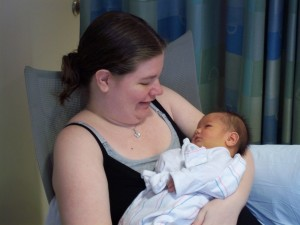 image is of a mom holding her dark haired newborn, smiling at his handsome face