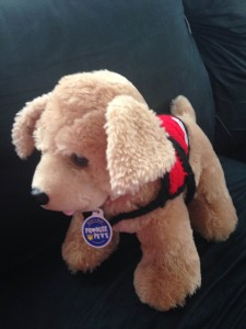 a stuffed golden retriever wearing a crocheted red service vest